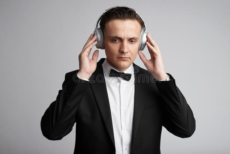 Concentrated attractive young man in headphones listening to music. Isolated on grey background royalty free stock photos