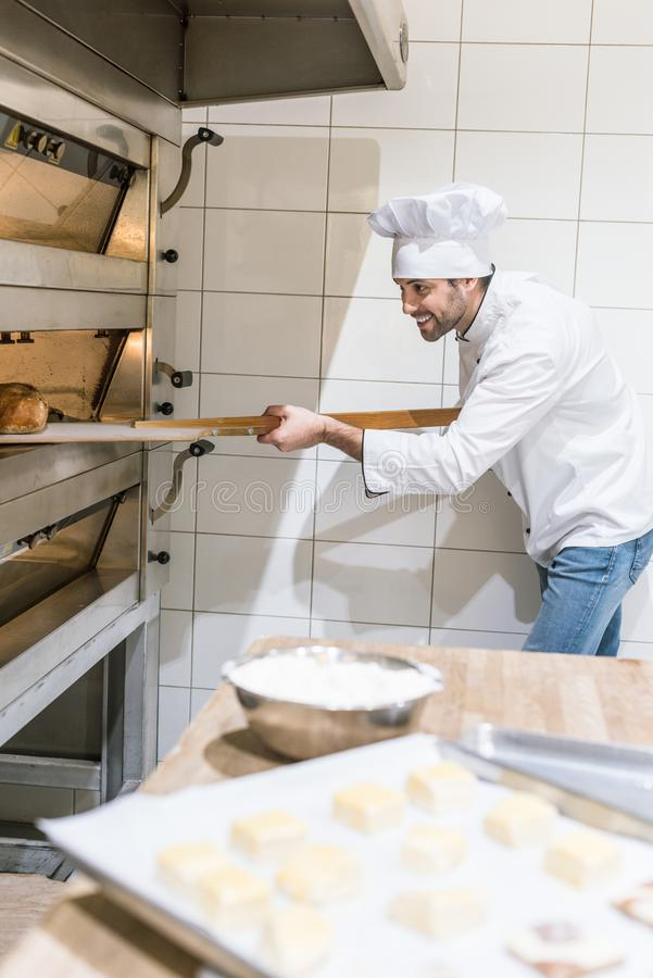 Concentrated baker taking out hot bread from oven. At kitchen royalty free stock photography