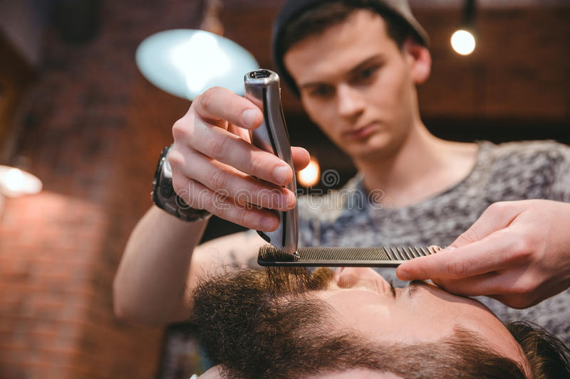 Concentrated barber making perfect beard to handsome bearded man royalty free stock photography