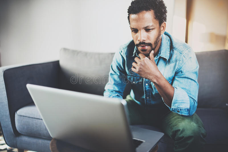 Concentrated bearded African man working at home while sitting on the sofa.Using laptop for new job search.Concept of royalty free stock photography