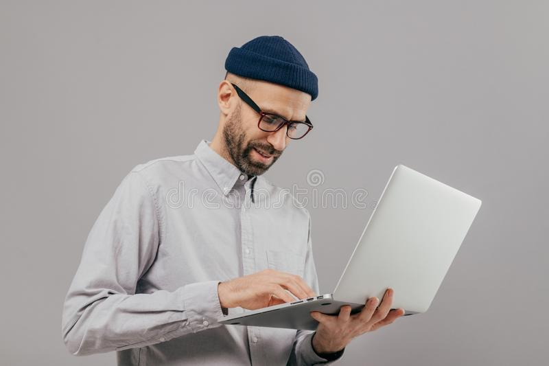 Concentrated bearded male administrative worker coordinates work on distance, searches information on laptop computer, wears white. Formal shirt and transparent royalty free stock photos