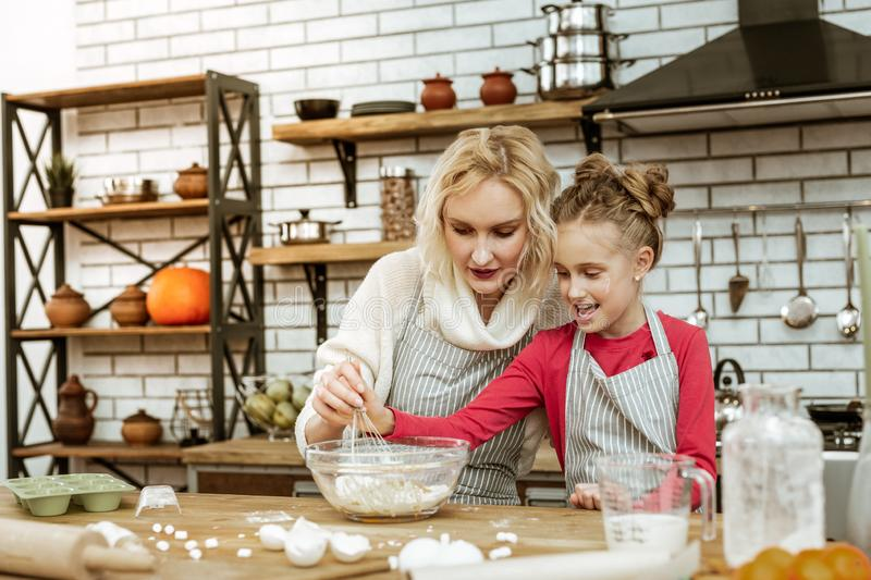Concentrated beautiful woman using metal whisk for mixing. Cooking sphere. Concentrated beautiful women using metal whisk for mixing while sitting at the wooden stock photo