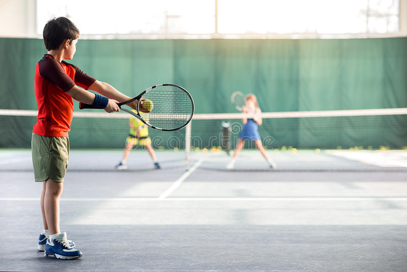 Concentrated boy pitching tennis ball stock photos