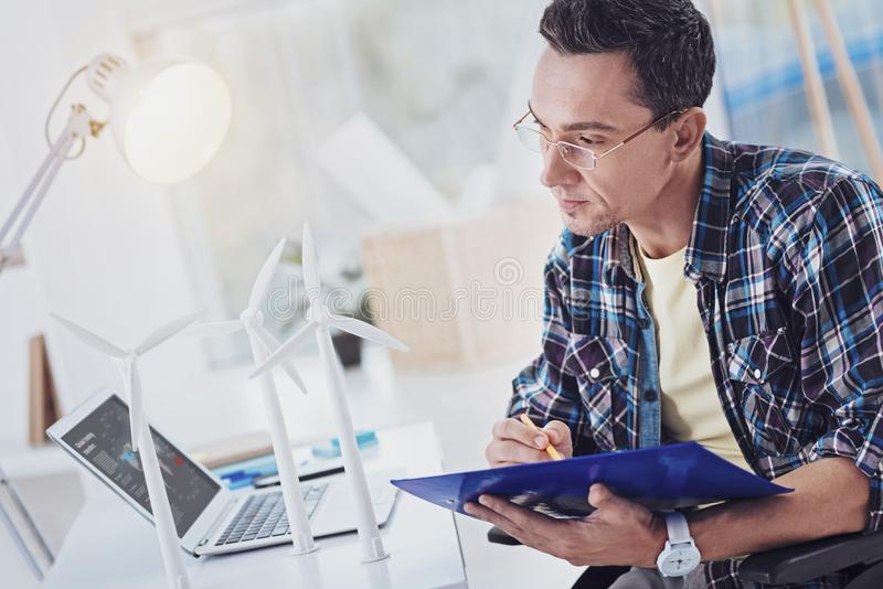 Concentrated brunette man making notes royalty free stock photo