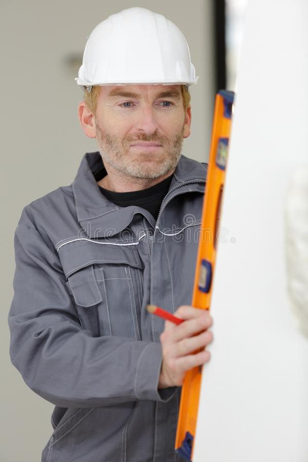 Concentrated builder keeping special tool. Man royalty free stock photos