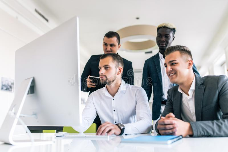 Concentrated business team discussing presentation together in office. Serious young multiethnic business expert preparing report royalty free stock photos