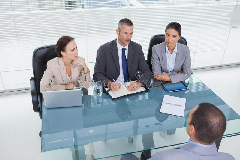 Concentrated business team interviewing experienced man stock image