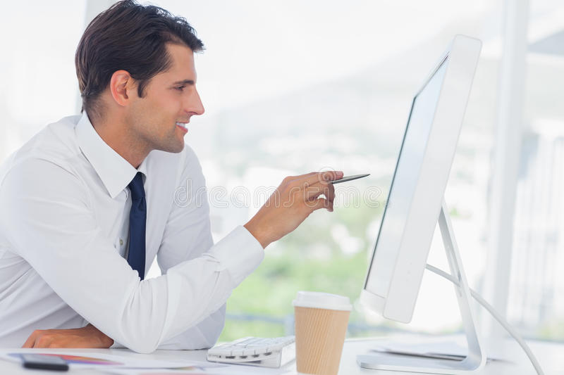 Concentrated businessman analyzing documents on his computer screen. Concentrated businessman in his office analyzing documents on his computer screen stock photos