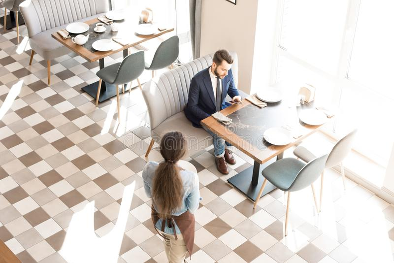 Concentrated businessman checking phone while waiting food in ca. Directly above view of pensive concentrated young businessman sitting at table and using royalty free stock images