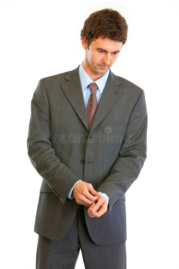 Concentrated businessman correcting cuff link royalty free stock photos
