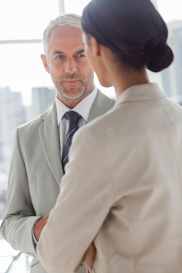 Concentrated businessman listening to colleague. In the office stock photo