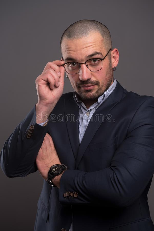 Concentrated businessman looking at you while touching the rim of his glasses. Attentive handsome director touching the rim of his glasses while looking at you royalty free stock photo