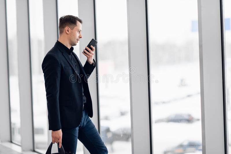 Concentrated businessman recording voice message at airport.  stock photo