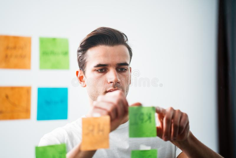 Concentrated businessman standing at office space behind glass wall with sticky notes stock photos