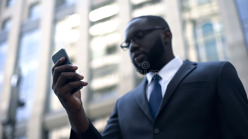 Concentrated businessman using smartphone for work, trading online, internet stock photo