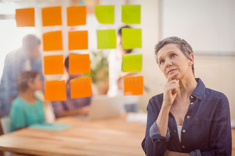 Concentrated businesswoman looking post its on the wall royalty free stock image