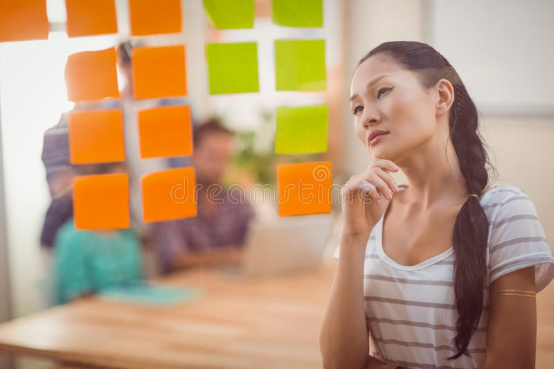 Concentrated businesswoman looking post its on the wall. In the office royalty free stock images