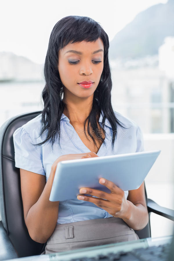 Concentrated businesswoman using a tablet pc. In office stock image