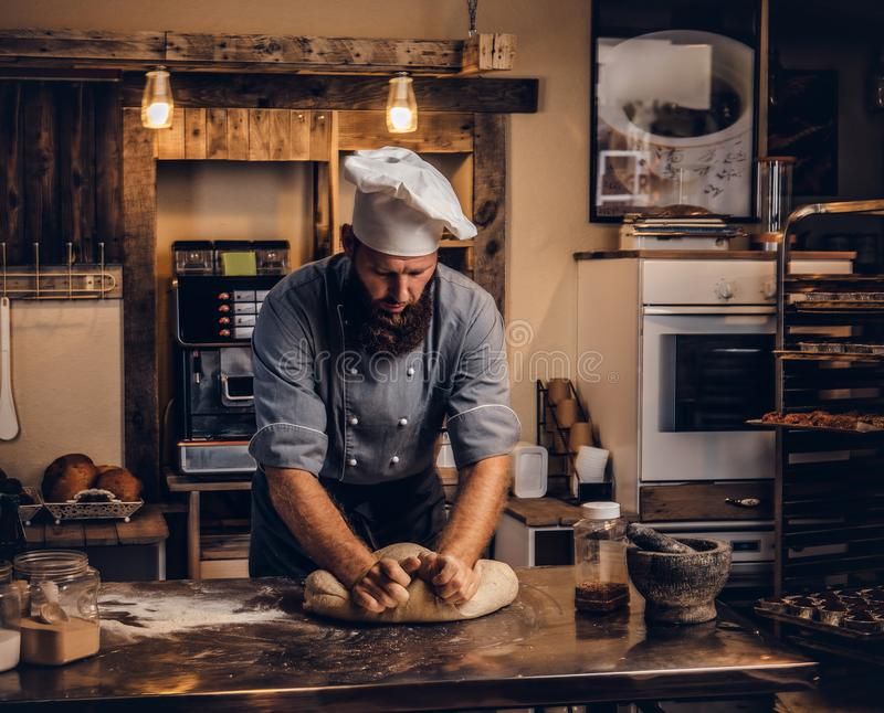Concentrated chef kneading dough in the kitchen. stock images