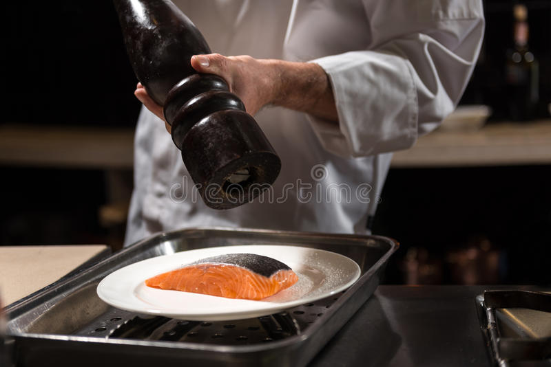 Concentrated chef putting salt on the salmon steak stock image