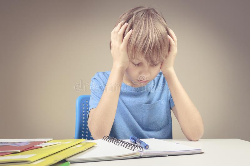 Concentrated child doing his homework at home. The boy sitting and looking in to books and notebooks. stock photos
