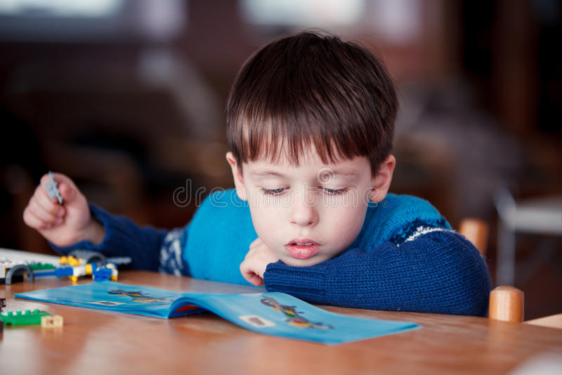 Concentrated child reading a manual. Before do-it-yourself project stock photography