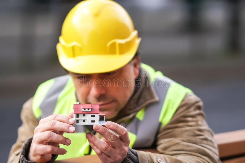 Concentrated civil engineer with a scale model of a house. Concentrated civil engineer using a house scale model. Outdoors royalty free stock images