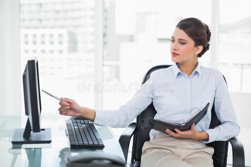 Concentrated classy brown haired businesswoman checking her agenda. In bright office royalty free stock images