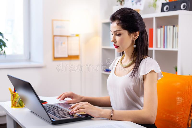 Concentrated cold beautiful woman with bulky jewelry. Younger beautiful lady . Concentrated cold beautiful woman with bulky jewelry dealing with laptop at work stock photos