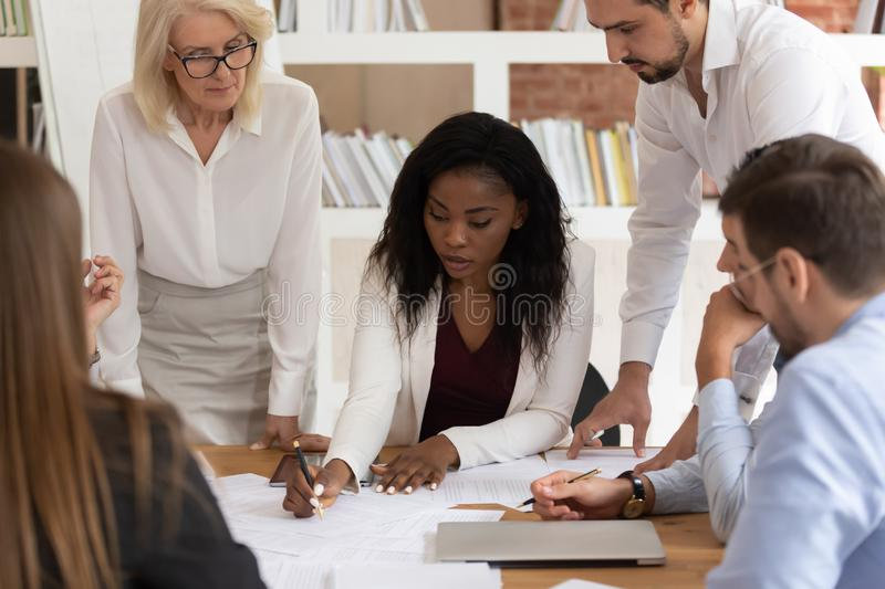 Concentrated colleagues brainstorm discussing paperwork at briefing. Focused african American businesswoman explain discuss paperwork project with diverse royalty free stock photo
