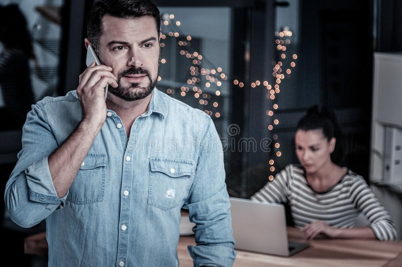 Concentrated confident man looking aside and having phone conversation. royalty free stock photography