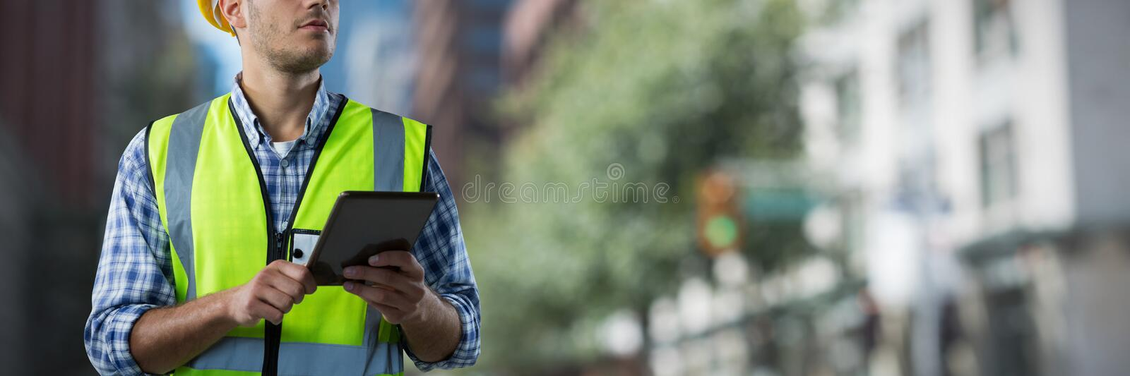 Composite image of concentrated construction worker with tablet royalty free stock photo