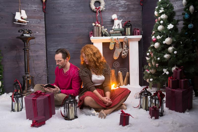 Concentrated couple looking at mobile phone against Christmas background. Attentive middle aged couple sitting on soft carpet at Christmas tree while looking at stock photos