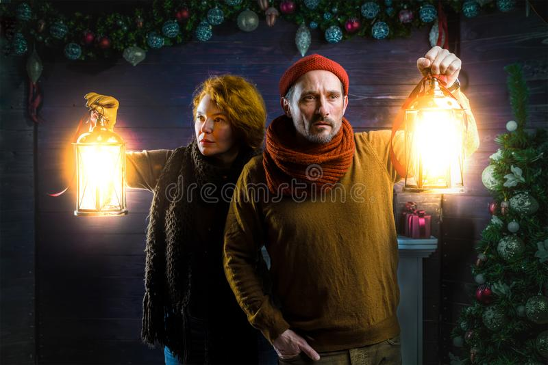 Concentrated couple scrutinizing the house while using hand lanterns stock photos