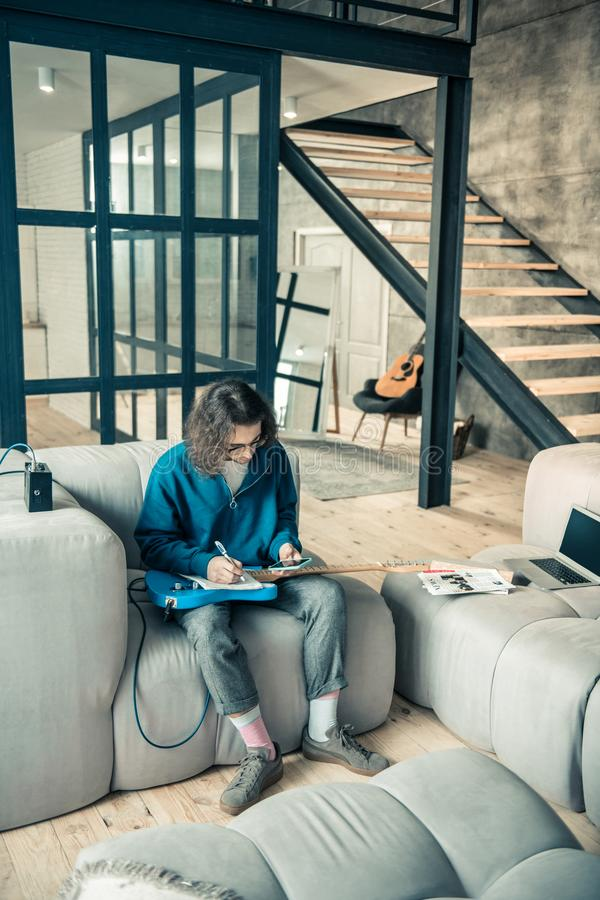 Concentrated dark-haired guitarist in clear glasses checking his smartphone. Writing down notes. Concentrated dark-haired guitarist in clear glasses checking his royalty free stock photo