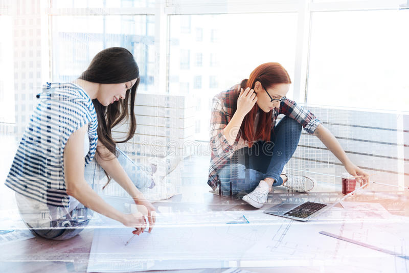 Concentrated designers working on the floor royalty free stock photo