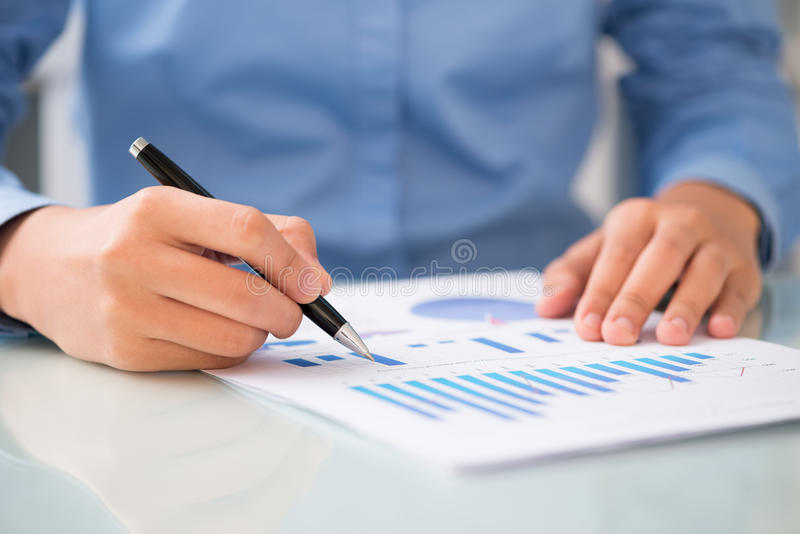 Concentrated on the diagram. Close-shot of male hands holding a ballpoint and analyzing the financial diagram royalty free stock photos