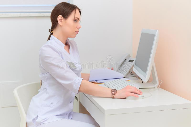 Concentrated doctor with report looking at computer monitor at desk in medical office. Concentrated doctor with report looking at computer monitor in medical stock images