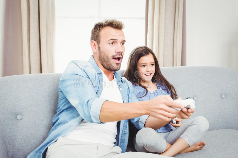 Concentrated father and daughter playing video game. At home stock images