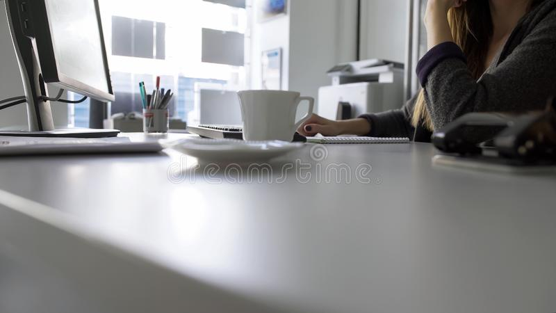 Concentrated female journalist thinking about article, sitting at computer stock photos
