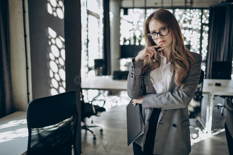 A Concentrated Female Manager Standing and Thinking royalty free stock image