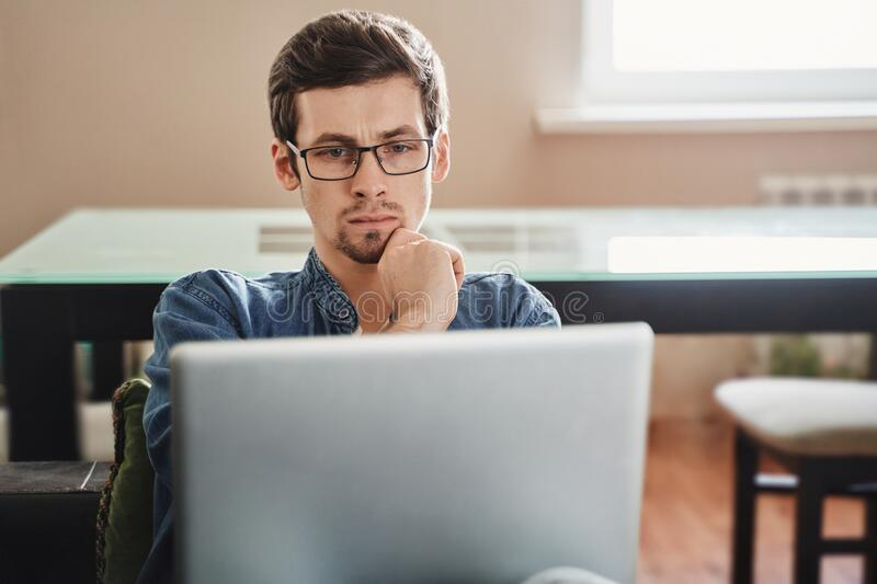 Concentrated freelancer in glasses looking at laptop display at home. Focused young businessman in eyewear looking at laptop at home, disappointed with bad news stock photography