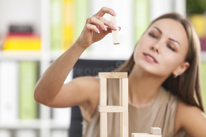 Concentrated girl is playing with wood bricks. Concentrated woman in beige is playing with wooden bricks at her workplace in a white office. Concept of a break royalty free stock photography