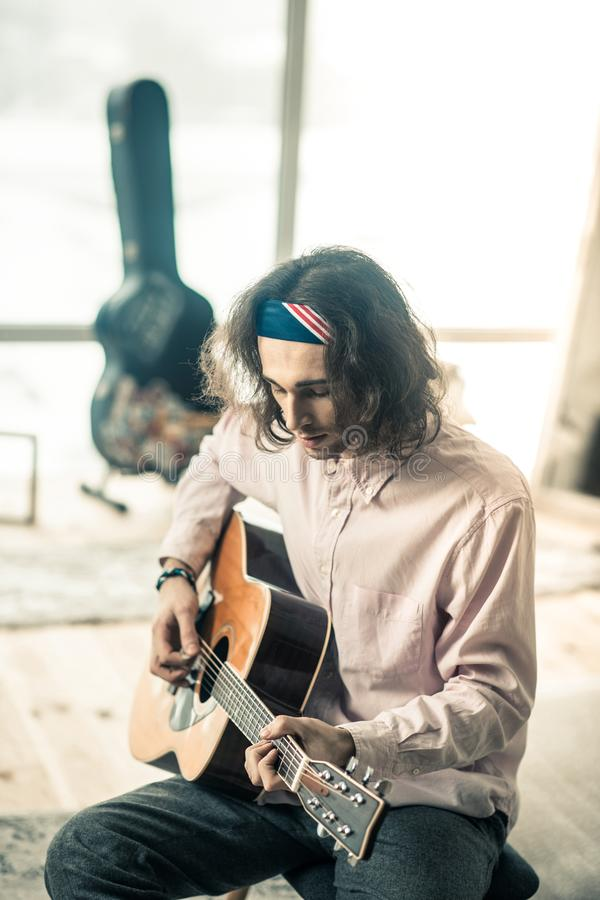 Concentrated good-looking artist in colorful bandana twanging. Guitar sound. Concentrated good-looking artist in colorful bandana twanging on personal acoustic stock images