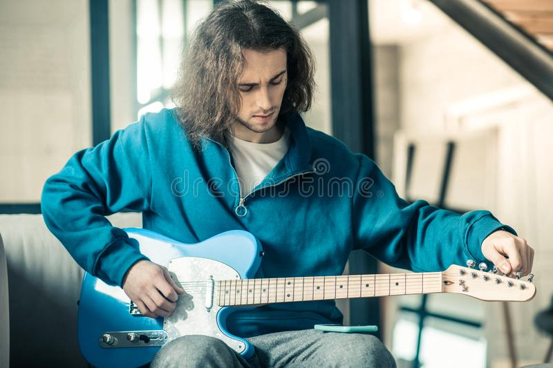 Concentrated good-looking unusual guy setting up strings on his electronic guitar. Carrying bright instrument. Concentrated good-looking unusual guy setting up stock photo