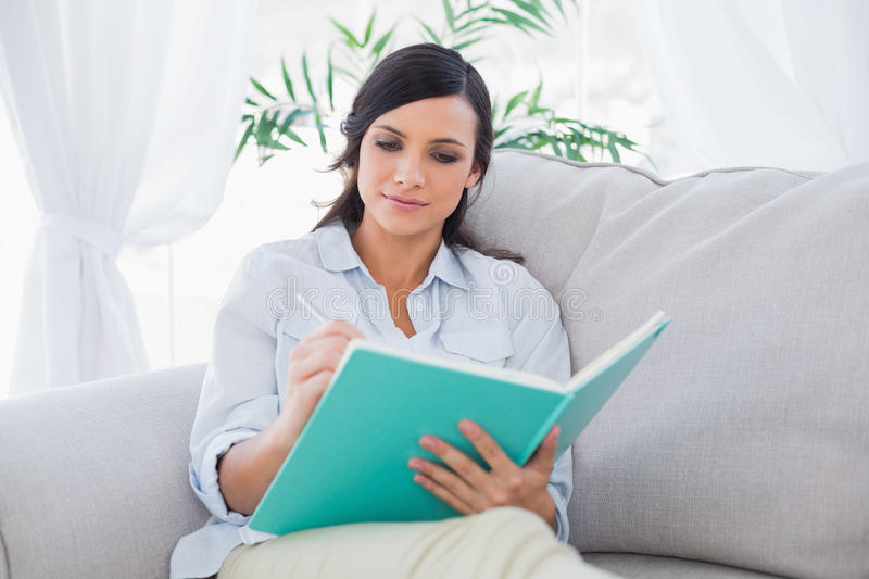 Concentrated gorgeous brunette writing while sitting on the sofa royalty free stock photo