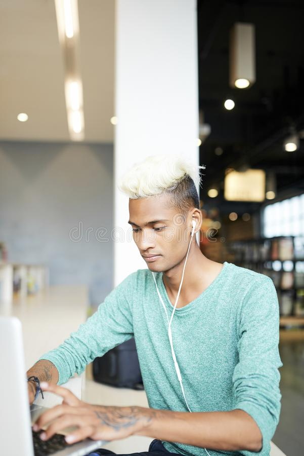 Concentrated guy using wifi in library. Serious concentrated young black guy in wired earphones sitting in library and searching for information on internet royalty free stock images