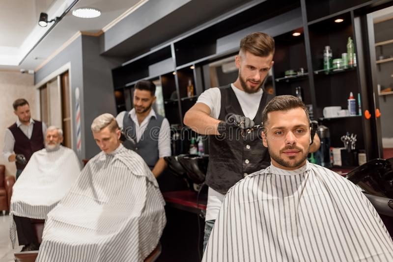 Concentrated hairdresser making professional and stylish haircut to client. stock photos