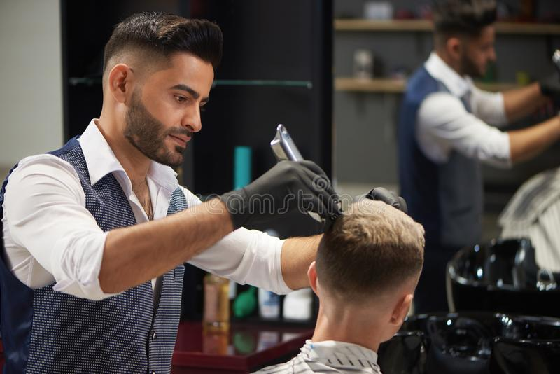 Concentrated hairdresser trimming haircut of client using trimmer. royalty free stock image