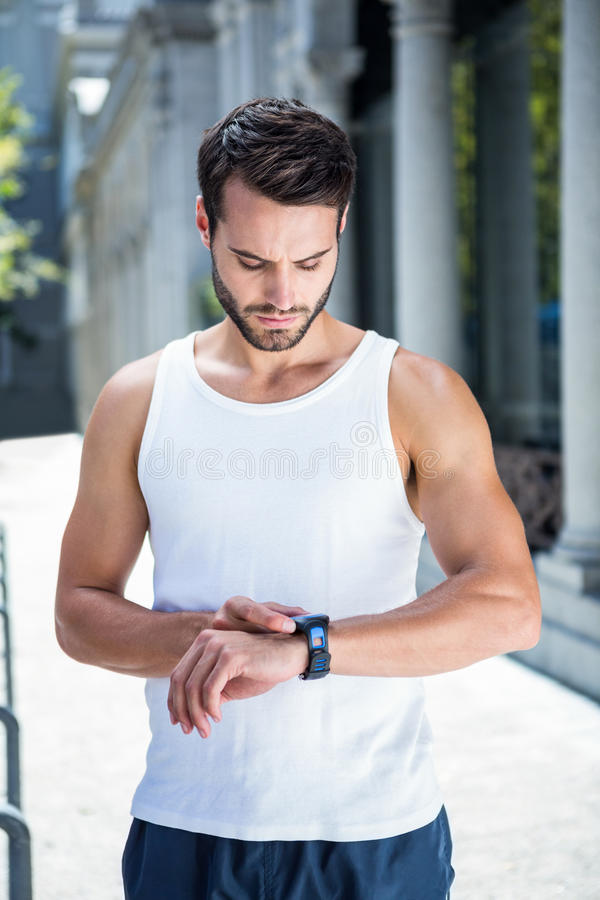 Concentrated handsome athlete setting heart rate watch stock images